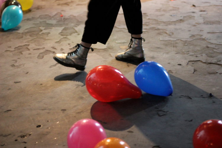 a person wearing silver dr martens walking across a floor with colourful ballooons