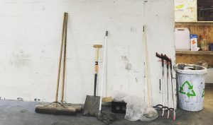 a broom, litter pickers, and shovel in front of a white wall in the Partisan basement